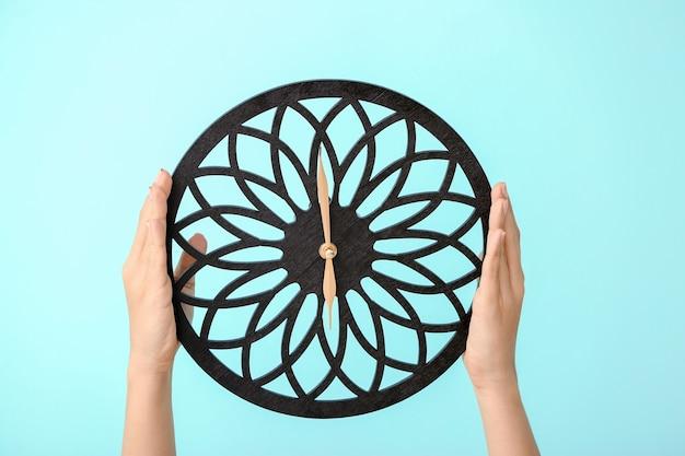 Orologio della holding della donna sul colore. concetto di gestione del tempo