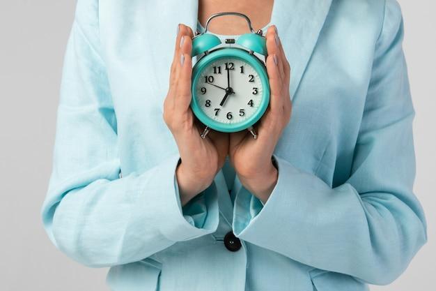 Donna che mantiene l'orologio in mano