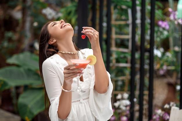 Donna che tiene un cocktail e una ciliegia nelle sue mani