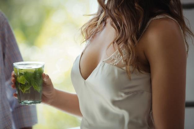 Donna che mantiene un bicchiere da cocktail nel ristorante