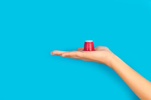 Donna che tiene una capsula di caffè sul palmo della mano