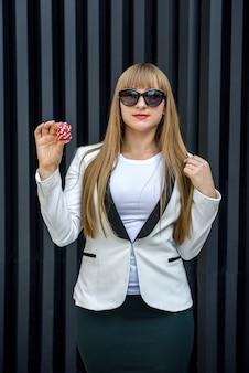 Donna che tiene fiches da poker colorate su sfondo astratto. tema del gioco d'azzardo