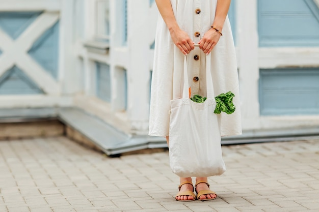 Donna che tiene il sacchetto della spesa in cotone con verdure e bottiglia d'acqua. borsa ecologica riutilizzabile per lo shopping. rifiuti zero concetto.