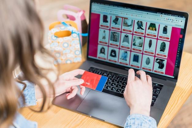Carta di credito della tenuta della donna davanti al computer portatile con il sito web di acquisto