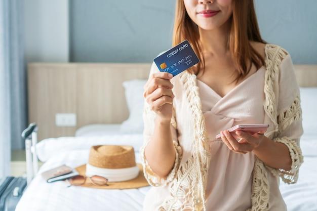 Donna in possesso di carta di credito, smartphone con accessori da viaggio sul letto. concetto di società senza contanti