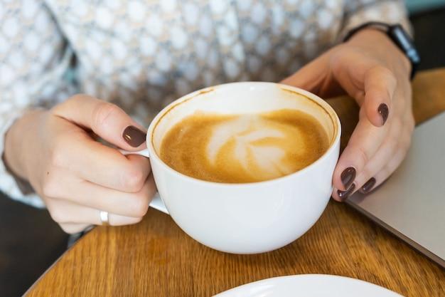 Donna che tiene una tazza di cappuccino
