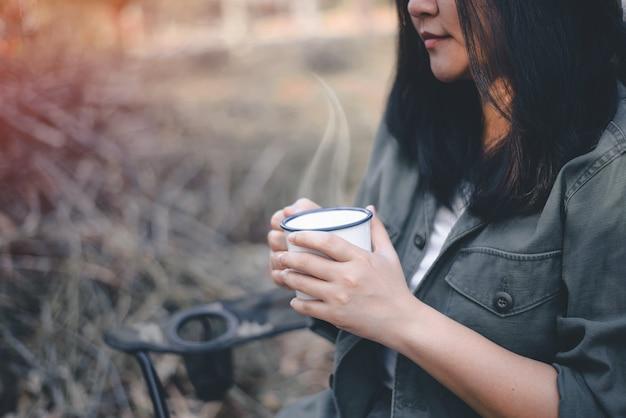 Donna che tiene una tazza di caffè durante il campeggio