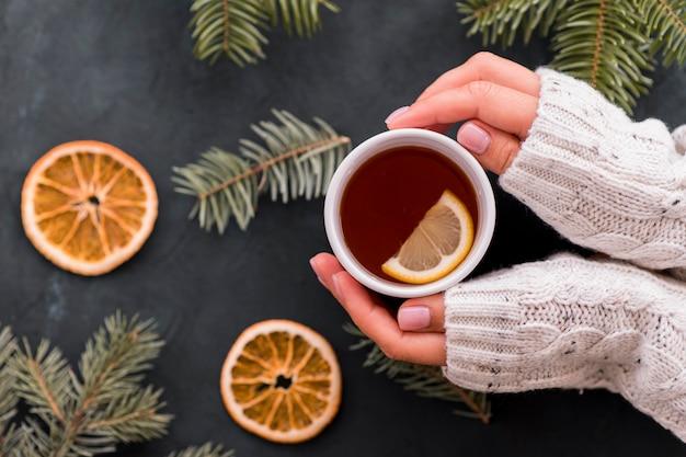 Donna che tiene tazza di caffè con fette di limone