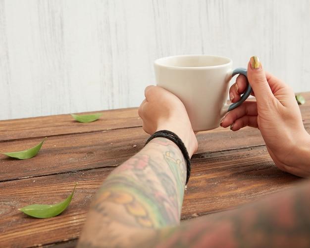Donna che tiene una tazza di tè aromatico caldo