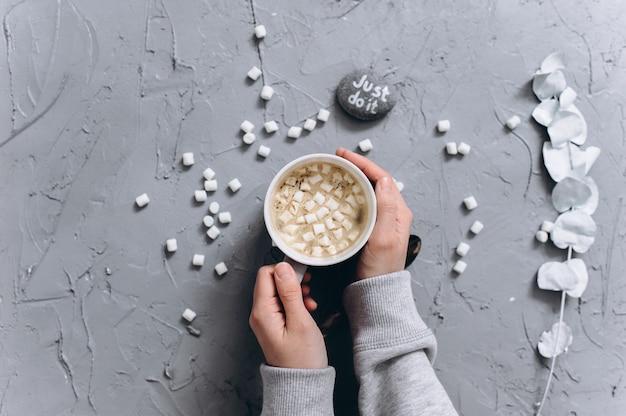 Donna che tiene tazza di caffè caldo, foto del primo piano delle mani in maglione caldo con la tazza, concetto di mattina di inverno, vista dall'alto