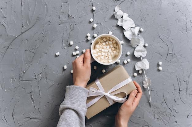 Donna che mantiene tazza di caffè caldo sul grigio tavolo cementato, foto del primo piano delle mani in un maglione caldo con tazza, concetto di mattina d'inverno, vista dall'alto