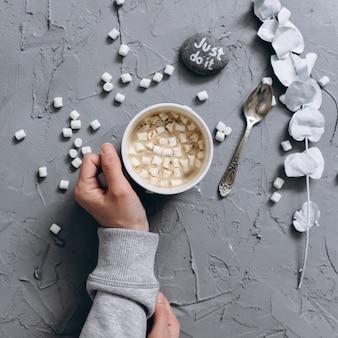 Donna che tiene tazza di caffè caldo sulla terra posteriore cementata rgray, foto del primo piano delle mani in maglione caldo con la tazza, concetto di mattina invernale, vista dall'alto