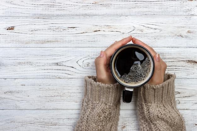 Donna che tiene tazza di caffè caldo sul tavolo in legno rustico