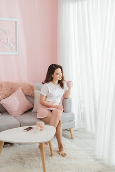 Donna che tiene tazza sorridente nel soggiorno