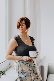 Donna che tiene una tazza di tè vicino alla finestra