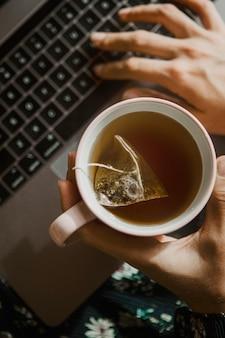 Donna che tiene una tazza di tè mentre usa un laptop