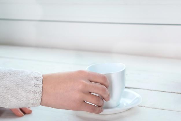 Donna che tiene una tazza con tè o caffè caldo vicino alla finestra di casa sua al mattino.