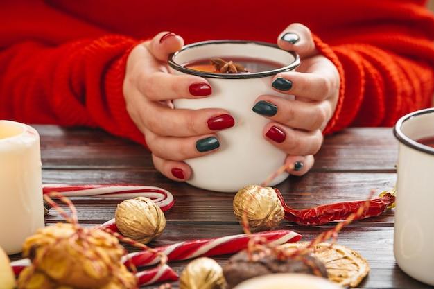 Donna che mantiene la tazza con vin brulè nelle sue mani