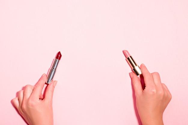 Donna che tiene rossetti scuri e chiari su sfondo rosa pastello. trucco da giorno contro concetto di trucco da notte. rosso scuro e rosa chiaro, rossetti nudi nelle mani di una donna su rosa pastello, vista dall'alto