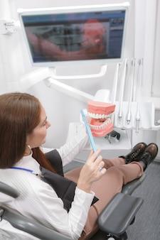 Donna che mantiene modello dentale e spazzolino da denti, seduto in poltrona odontoiatrica