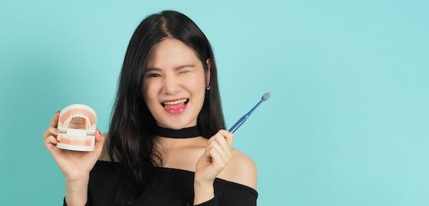 Donna che mantiene i denti dentali modello o modello ortodontico. concetto di cura orale.