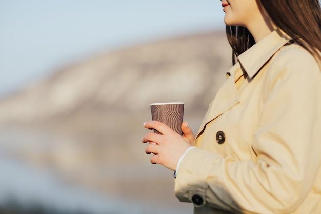 Donna che tiene tazza di caffè usa e getta