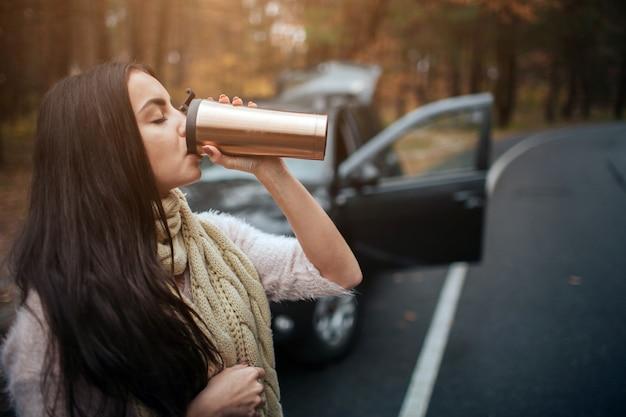Donna che tiene tazza di caffè eliminabile accanto all'automobile. primo piano a mano. concetto di autunno. viaggio nella foresta d'autunno in auto