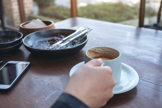 Una donna che tiene e beve caffè con il telefono cellulare sul tavolo di legno nella caffetteria