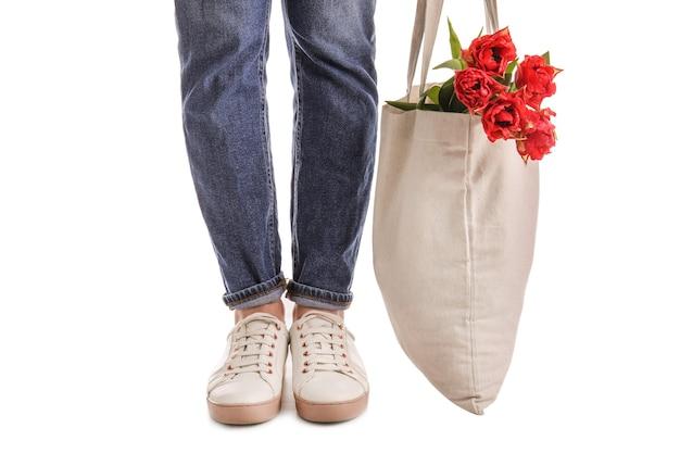 Donna che tiene la borsa ecologica con fiori su superficie bianca