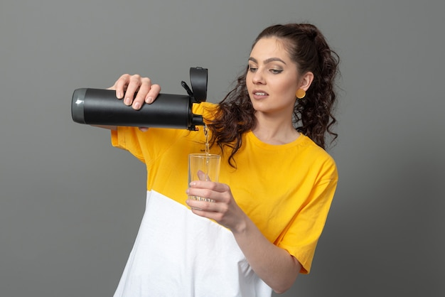 Donna che mantiene eco riutilizzabile smart termo bottiglia d'acqua con promemoria bevanda, concetto di stile di vita sano