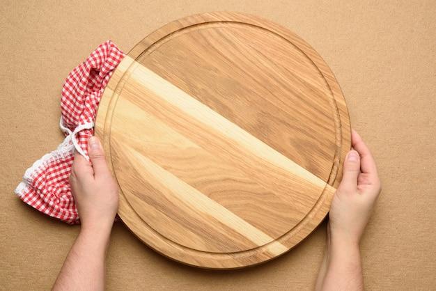 Donna che mantiene vuoto rotondo in legno pizza board in mano, corpo su uno sfondo marrone, vista dall'alto