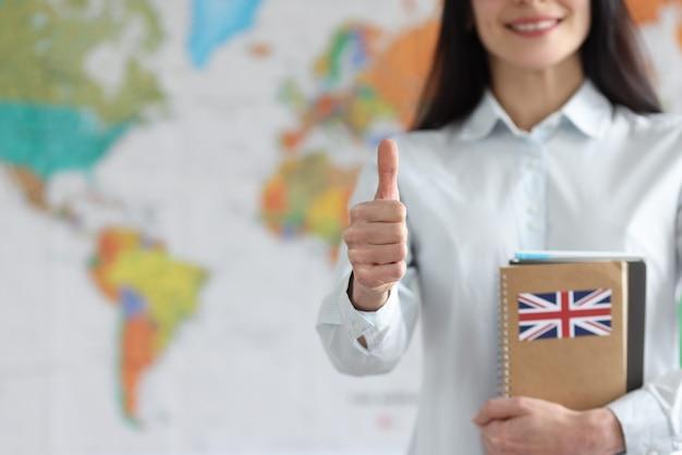Donna che tiene libri di testo inglesi sullo sfondo della mappa del mondo e che mostra il pollice in alto