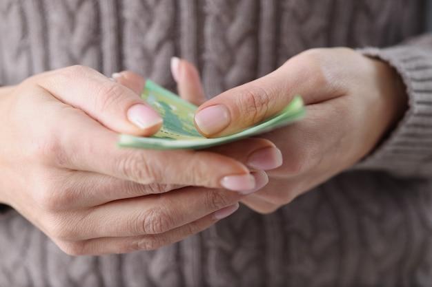 Donna che tiene le banconote in euro nelle sue mani concetto di contabilità domestica del primo piano