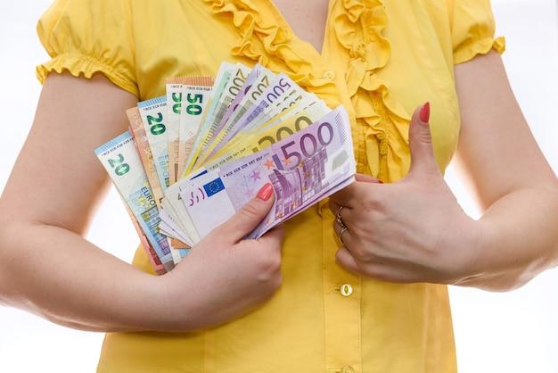 Donna che tiene in mano l'euro e mostra il pollice in su