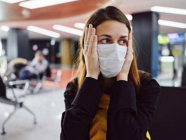 Donna che tiene la maschera nifiga facciale in attesa del ritardo del volo in aeroporto. foto di alta qualità