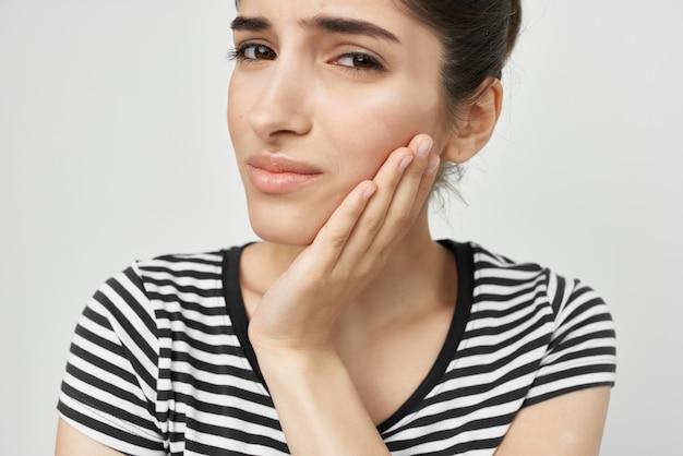 Donna aggrappata al viso mal di denti assistenza sanitaria sfondo isolato. foto di alta qualità