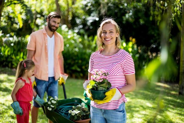 Vaso di fiore della tenuta della donna con la famiglia all'iarda