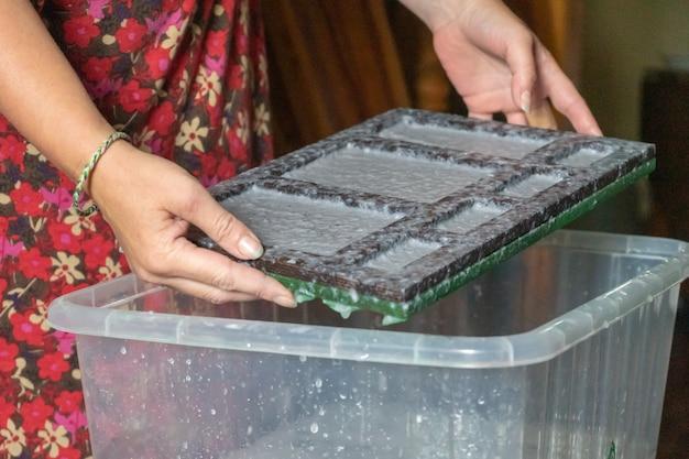 Donna che mantiene il telaio per la produzione di fogli di carta dalla pasta di carta straccia. messa a fuoco selettiva. arte decorativa e applicata. concetto di riciclaggio, ecologia.
