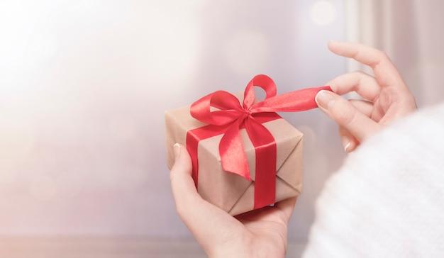 Donna che tiene una confezione regalo in mano e sciogliere un fiocco
