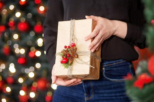 Contenitore di regalo della holding della donna con l'albero di natale dietro