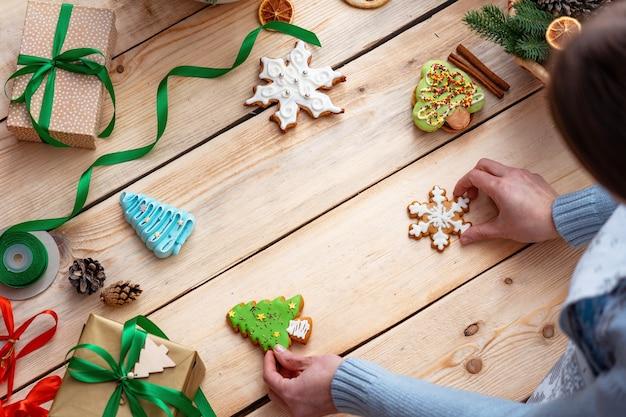 Donna che tiene un biscotto di panpepato su un tavolo in legno con ornamenti