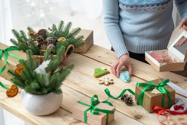 Donna che tiene un biscotto di pan di zenzero su un tavolo in legno con regali