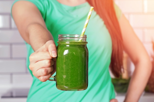 Donna che tiene un barattolo di vetro con un sano frullato verde