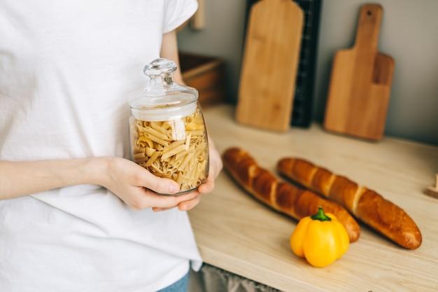 Donna che mantiene un barattolo di vetro con pasta di grano nella cucina moderna