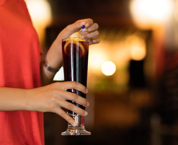 Donna con in mano un bicchiere di cocktail al limone al bar