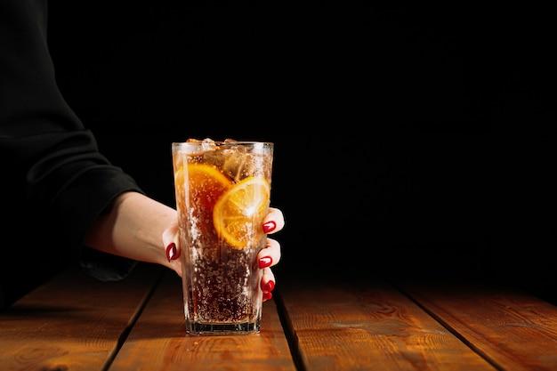 Donna che mantiene un bicchiere di tè freddo di long island