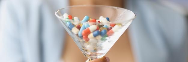 Donna che tiene il vetro con molte pillole multicolori nel primo piano delle mani