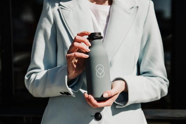 Donna con in mano una bottiglia grigia in acciaio inossidabile