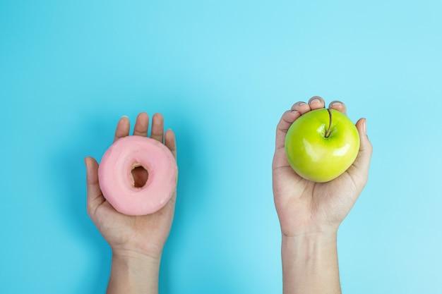 Donna che mantiene mela verde e ciambella rosa