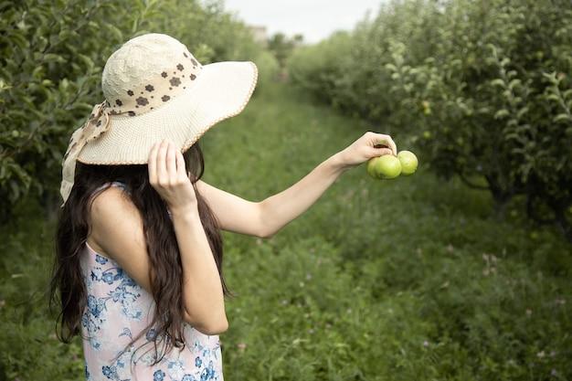 Donna che tiene le mele verdi in giardino